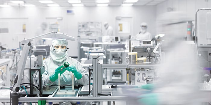 Assembly worker fabricating semiconductors and components in a Swagelok cleanroom